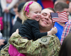 A soldier hugs his daughter after returning home from deployment