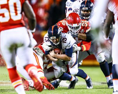 Denver Broncos quarterback Trevor Siemian (13) is taken down by Kansas City Chiefs defensive linemen Rakeem Nunez-Roches (99) and Bennie Logan (96)