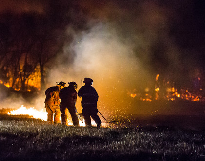 Firefighters work together to help put out a massive field fire near Knob Noster, Missouri