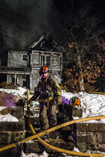 A firefighter responds to a house fire in the early hours of the morning in Warrensburg, Missouri in the winter of 2013