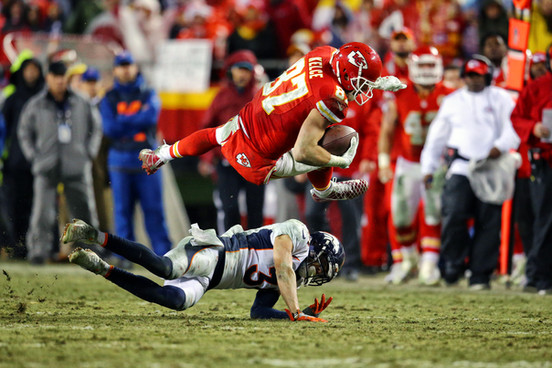 Kansas City Chiefs tight end Travis Kelce (87) leaps over Denver Broncos safety Justin Simmons (31)