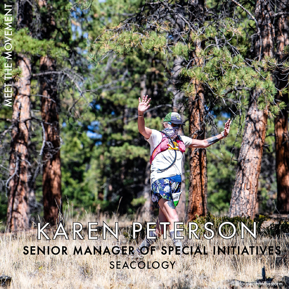 Karen Peterson, Senior Manager of Special Initiatives at Seacology, with her arms raised during a hike in a forest