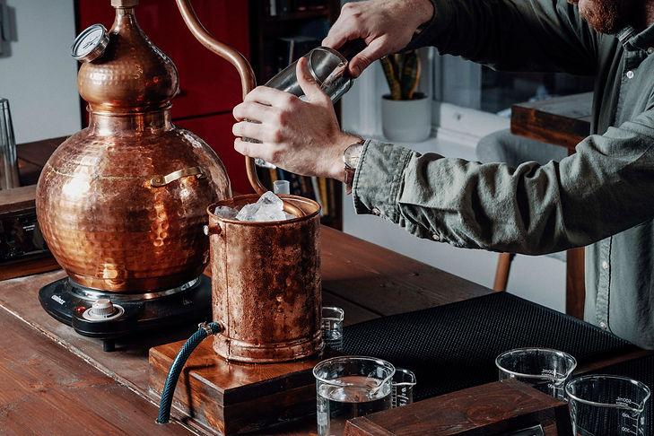 Person Distilling Spirits in Copper Pot Still