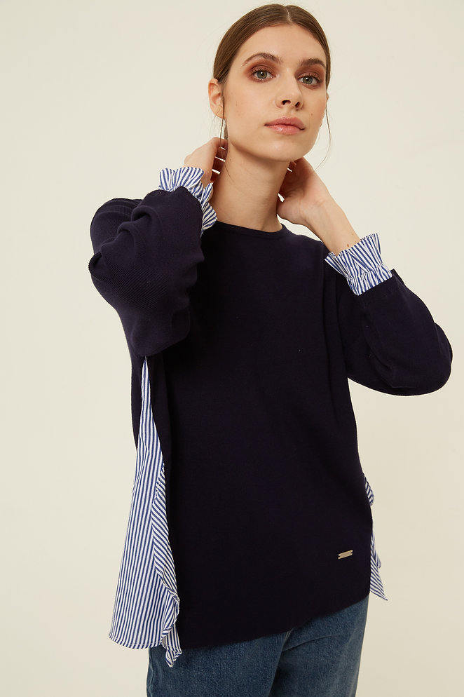 Woman wearing navy jumper with hem and cuff pinstripe shirt details