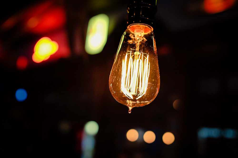 Light bulb illuminated with other color lights in background