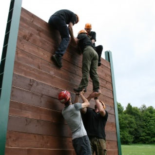 Group of adults climbing a wall at Stanley Head OEC