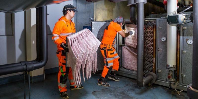IVaeris OY:n asentajat Hacen ja Gabi vaihtavat tuloilmasuodattimet suuressa ilmanvaihtokoneessa