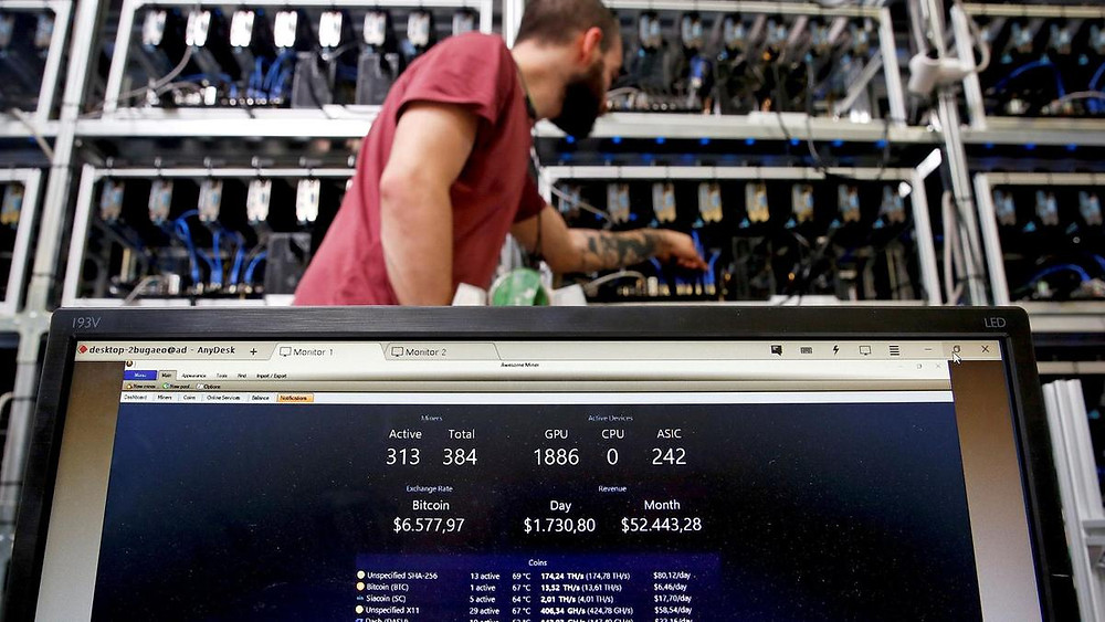 An employee works on a Bitcoin mining computer as a PC screen shows the fluctuations in Bitcoin exchange rates at Bitminer Factory in Florence, Italy. The cryptocurrency's performance over the past 10 years, even with its huge run-up and subsequent mega-crash, leaves all others in the dust. Reuters