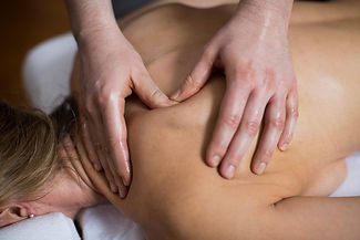 massage therapist providing massage to loosen a stiff back