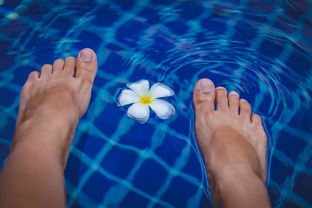 happy feet relaxing in water after reflexology treatment