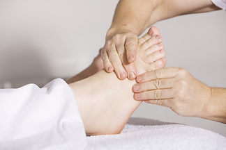 reflexologist applying pressure to the foot reflexes during reflexology treatment
