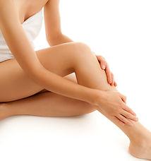 Vrouw die haar handen op haar onderbenen legt