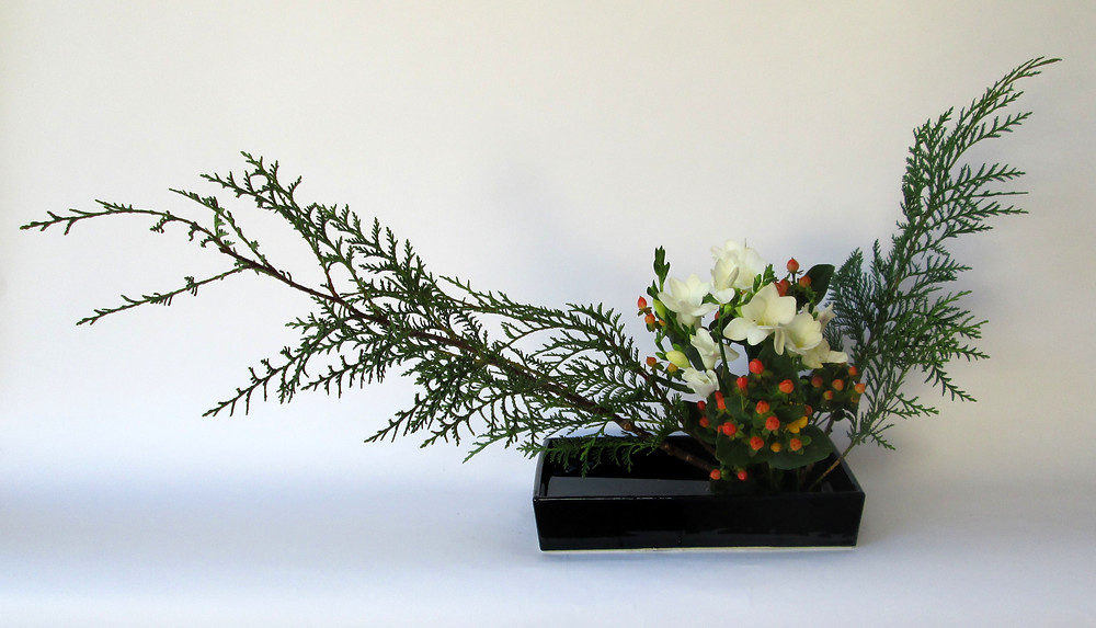Japanese ikebana flower arrangement with cedar and freesia.