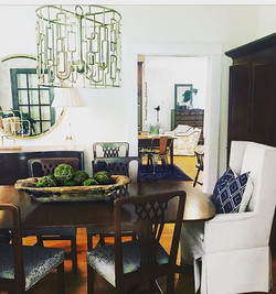 This dining room maintains tradition but with fresh paint, lighting, fabric and a big round gold mir
