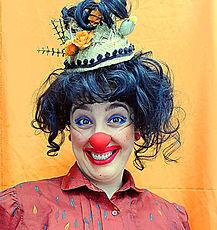 Palhaça Papoula, fundo laranja sorrindo e olhando para a câmera.