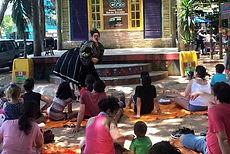 Público sentado no chão e, ao fundo, a Palhaça Papoula com um vestido grande e um quadril enorme, como se estivesse alguém sendo sua perna e parte de trás.
