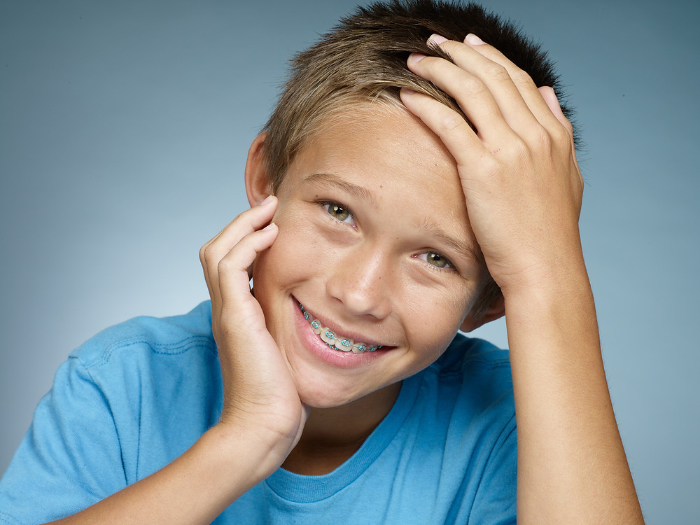Boy smiling with braces in blue shirt