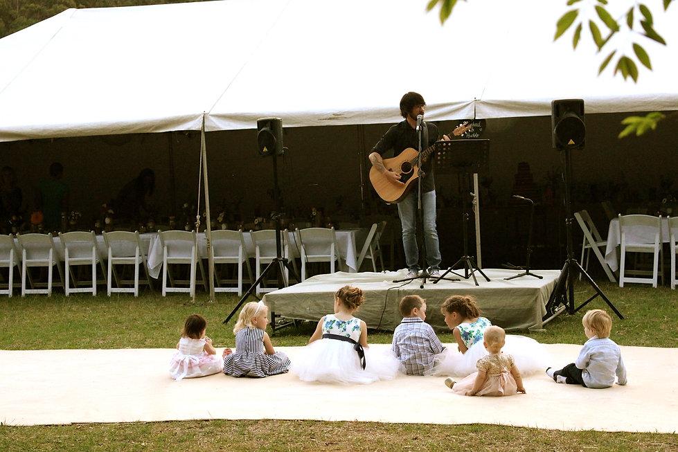 Brad Stokes playing music to children at wedding
