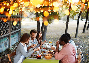 A group of people gathering for a meal around an outdoor table.