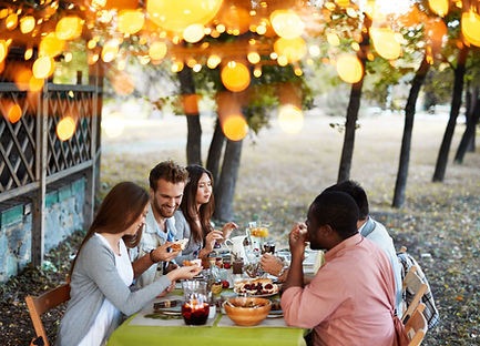 Five people having an outdoor dinner under warm lights
