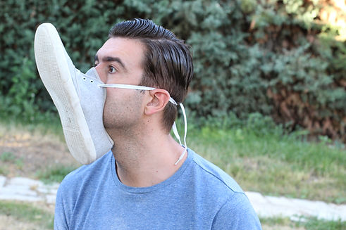 Man covering mouth and nose with shoe  .