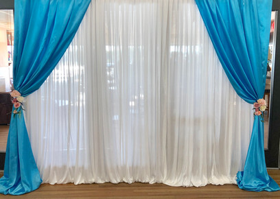 White Backdrop with blue draped sides.