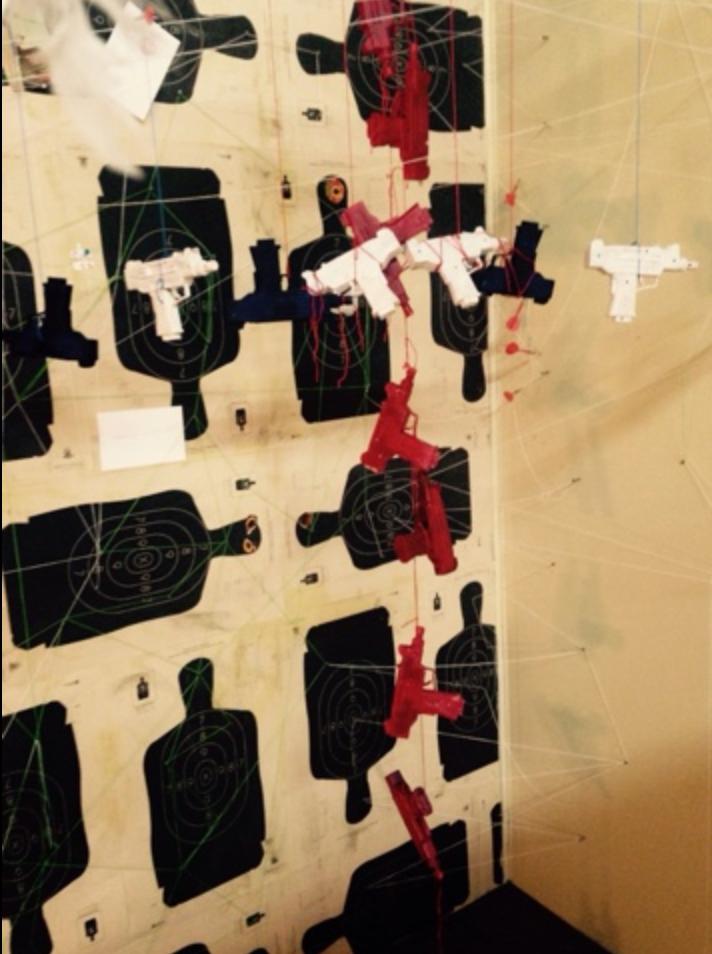 detail showing hanging cross made of painted guns