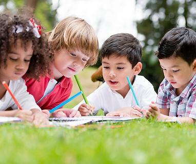 Children doing homework in the grass