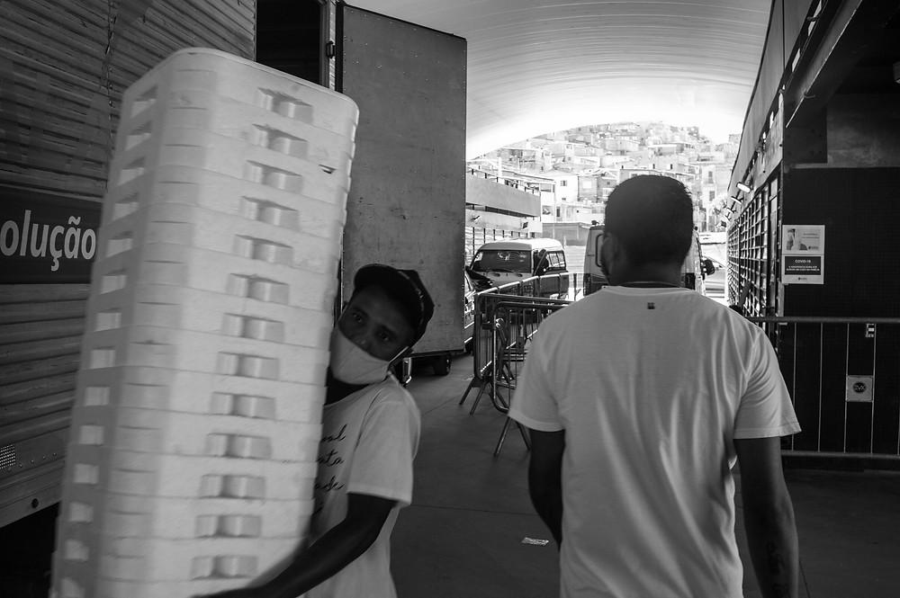 Voluntários carregam mantimentos na base de emergência em Paraisópolis contra a Covid-19