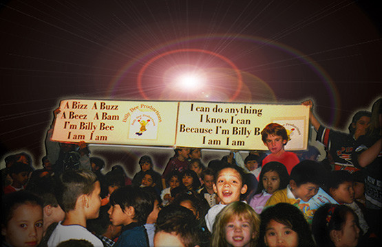 One of the school presentations by the author Peter Thomas and the students are holding up a sign with the Billy Bee Motto printed on it. A Bizz, A Buzz, A Beez, A Bamm, I'm Billy Bee, I Am, I Am,  I Can Do Anything, I Know I Can, Cause I'm Billy Bee, I Am, I Am!