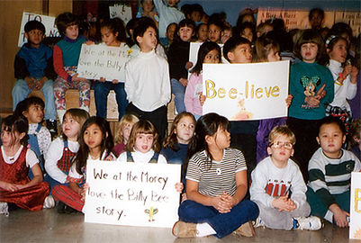 Elementary school children holing up signs telling how much they love the Phonological awareness in the stories