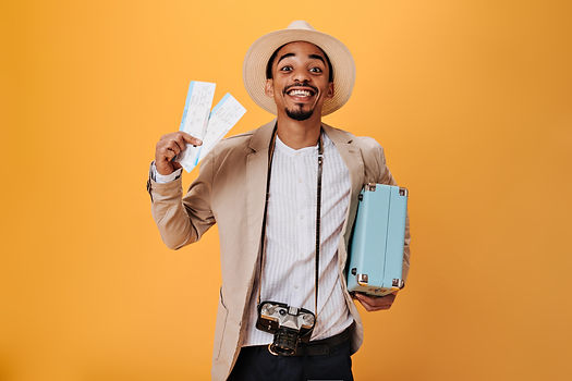 young-man-shirt-hat-holding-tickets-suitcase.jpg