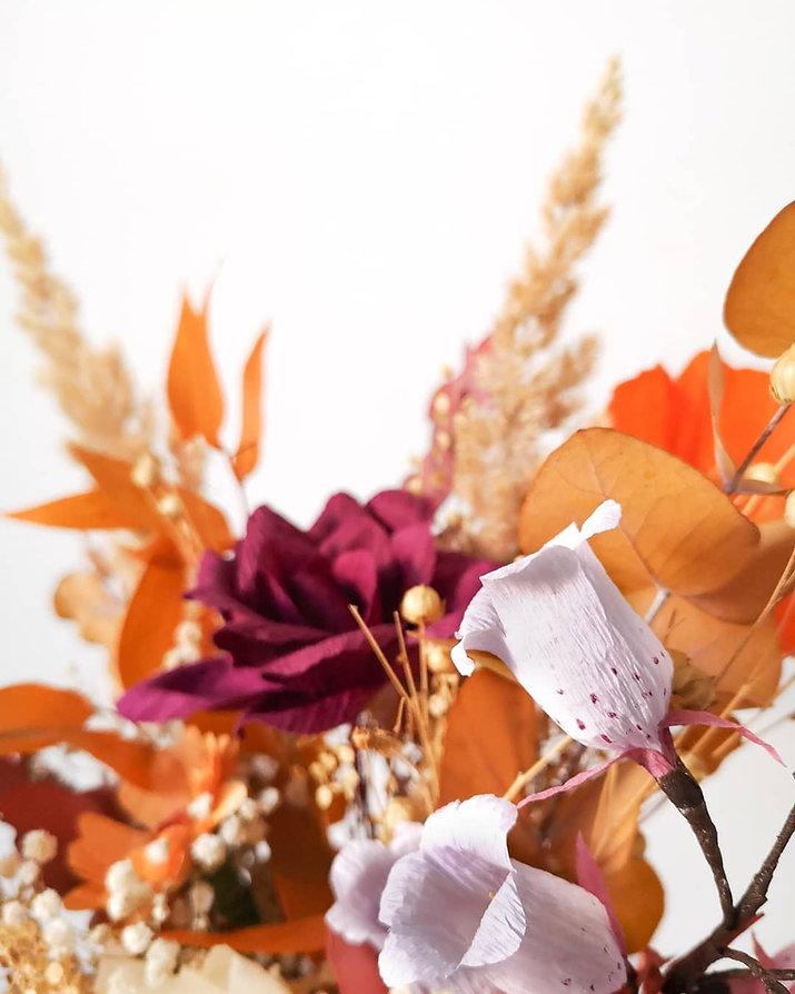Photo flouté d'un bouquet de fleurs séchées et fleurs en papier sur fond blanc