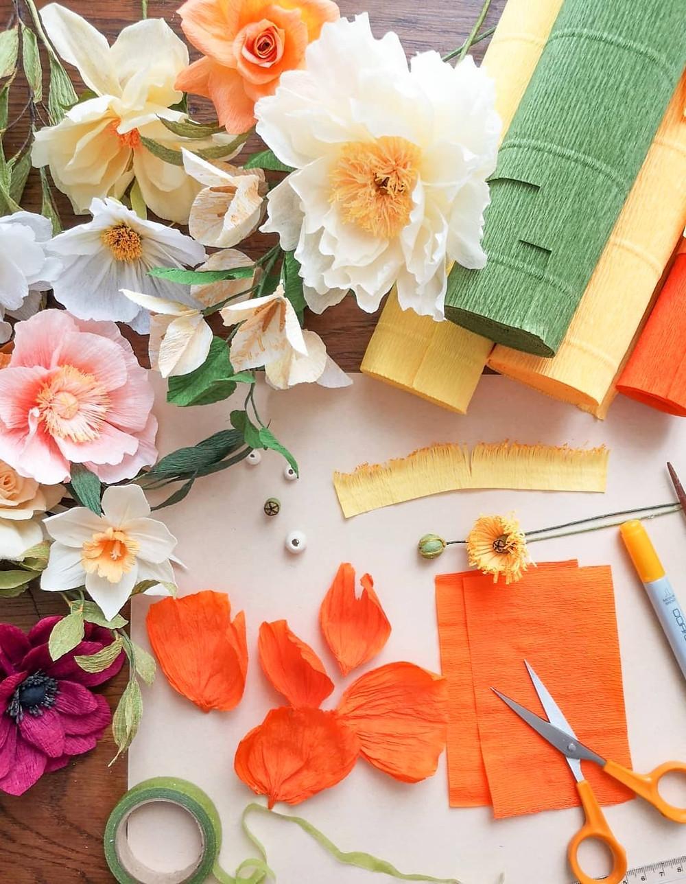 Plan de travail avec des fleurs en papier crépon de toutes les couleurs, des rouleaux de papier crépon et un pavot orange en cours de création