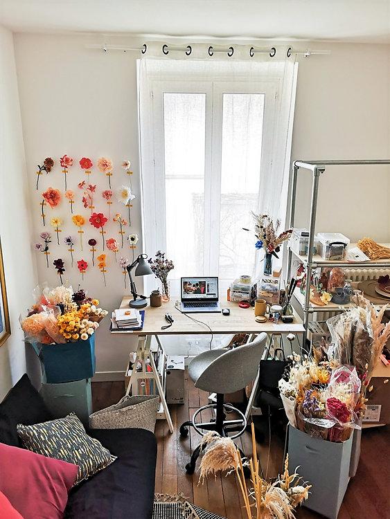 Mon espace de travail rempli de fleurs, situé dans un appartement parisien haut de plafond. On y voit aussi mon mur de fleurs en papier