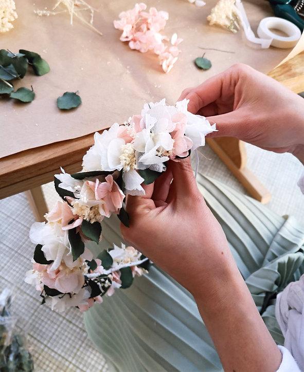 Photo d'une couronne de mariée en cours de réalisation. Couronne de tête faite de fleurs séchées et stabilisée dans les tons pastels