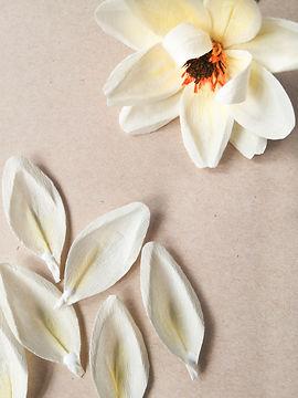 Dahlia fait main en papier crépon de haute qualité posé sur une table avec quelques pétales