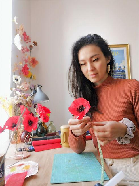 photo de moi, la créatrice d'Haïlane entrain de confectionner un coquelicot rouge en papier