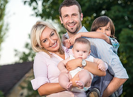 happy-family-posing-outdoors-in-front-of