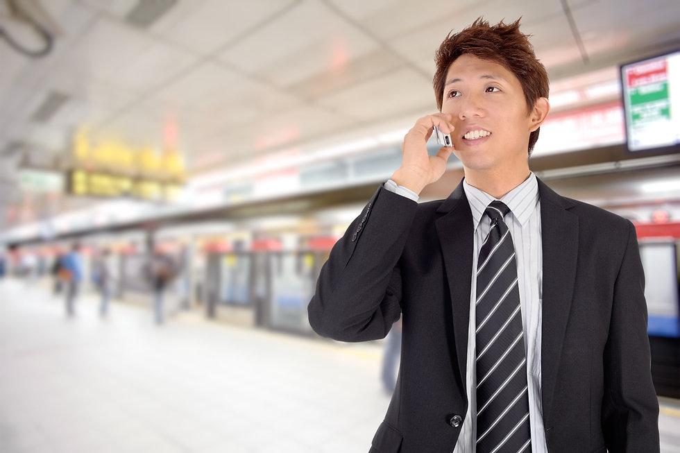 Smiling business man using cellphone in station._edited.jpg