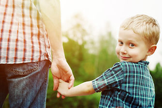 a little boy holding his dads hand as he looks back with a smile