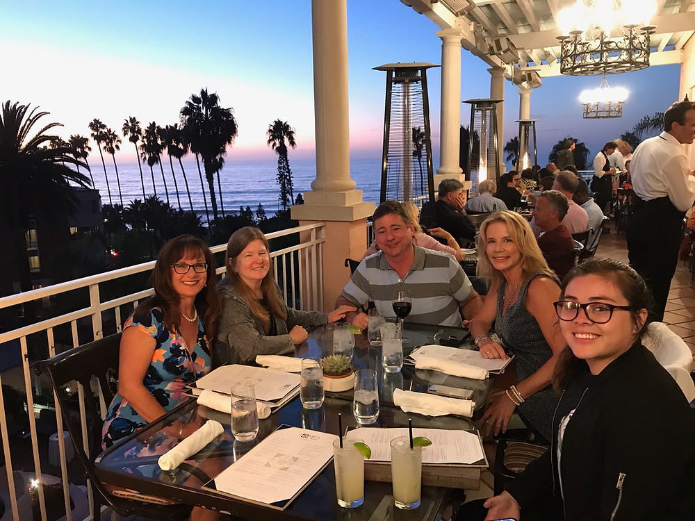Rick is sitting at a dinner table with a beach sunset in the background with his wife Megan, as well as some of his coworkers and patients.