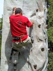 Don, A Bilateral Amputee, climbs a large plastic rock wall while wearing both of his prosthetic legs. He is already quite high up, but you can tell he is determined to make it to the top.
