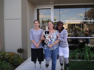 Lisa, a bilateral below knee amputee, is pictured on the far left with 2 of her friends who are also amputees. The girl in the center is holding Sky, who was a puppy at the time.