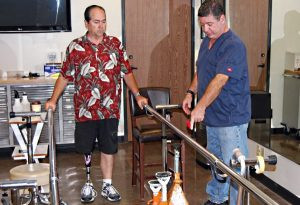 Above Knee Amputee Robert Poirier is practicing standing on his new leg at SCP while Rick watches.