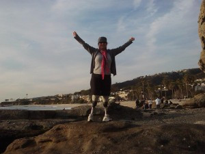 Deborah, a Bilateral Amputee, can be seen with her arms in the air doing a victory pose to celebrate conquering a hike with both of her prosthetic legs.