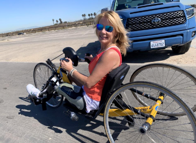 Above Knee Amputee Christy Flesvig is pictured hand cycling in Huntington Beach on a 3-wheeled bike while wearing her prosthetic leg.
