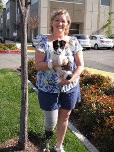 Diane is standing outside the old SCP building wearing her prosthetic. She is holding sky, who is only a puppy in this picture.