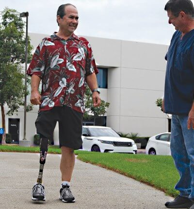 Above Knee Amputee Robert Poirier is walking on his new leg out front of SCP with Rick Myers.
