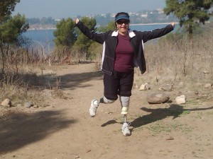 Deborah, a Bilateral Amputee, can be seen running down a hiking trail with a smile on her face and her arms in the air celebrating the outdoors.